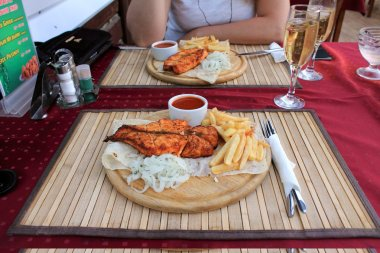 Fish fillet of salmon with condiments and garnish on the plate.