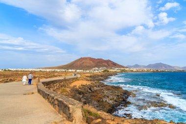 Tourists walking on coastal promenade along ocean in Playa Blanca