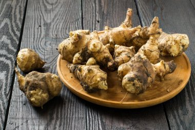 Fresh jerusalem artichokes on the board
