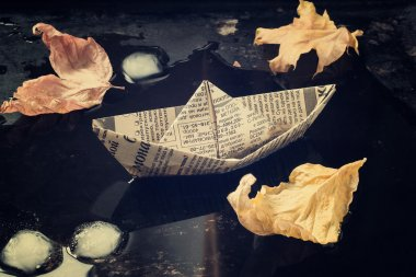 The mood of autumn: the leaves and a paper boat in the puddle. T