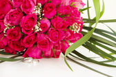 Fotografie snubní prsteny a svatební kytice růžových růží izolované nad whi