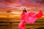krásná dívka v červených šatech na tropické moře při západu slunce pozadí
