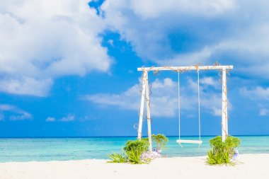 Wedding arch decorated with flowers on tropical sand beach, outd