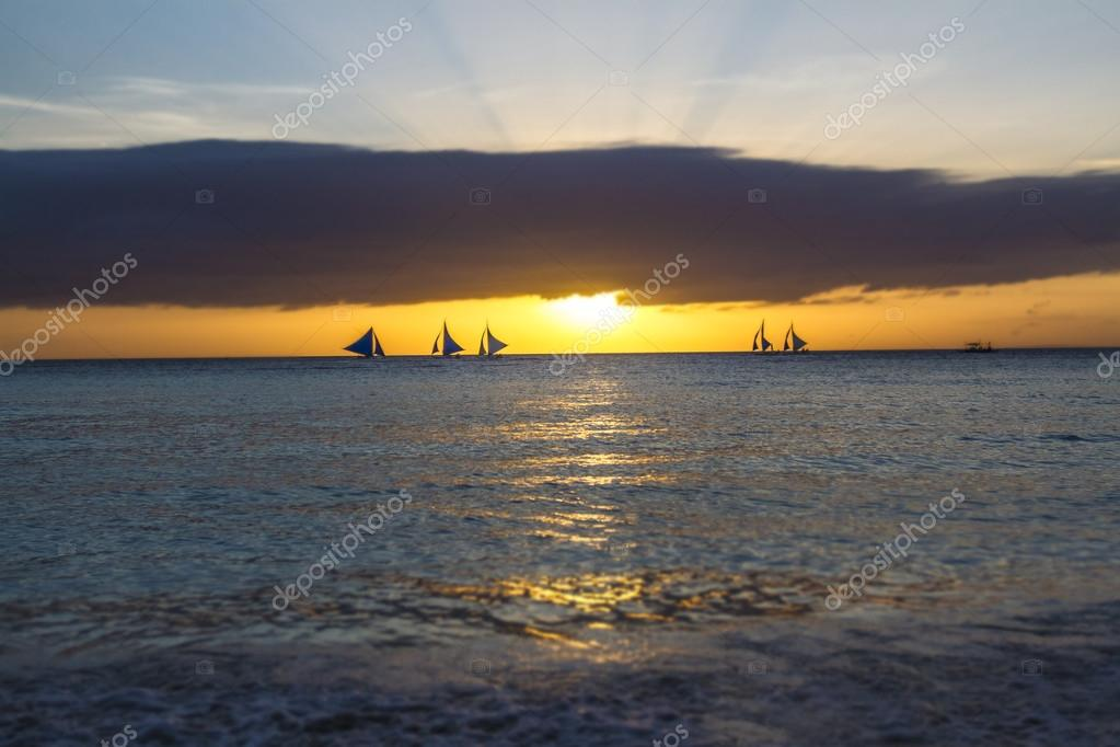 sailboats on sunset sea and sky background
