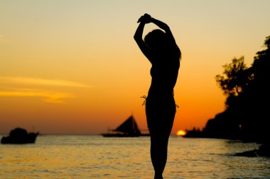 silhouette of young beautiful woman on tropical sunset sea backg