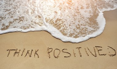 think positive written on sand beach - positive thinking concept