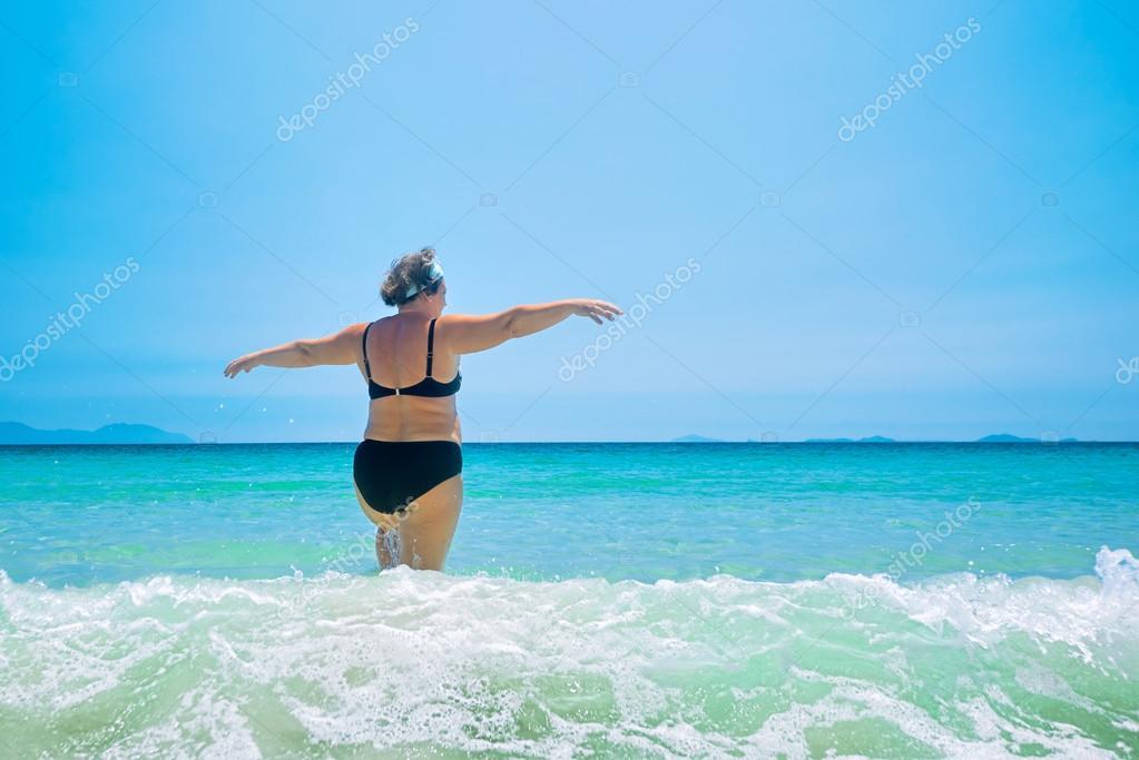 Donna matura in costumi da bagno al mare u foto stock