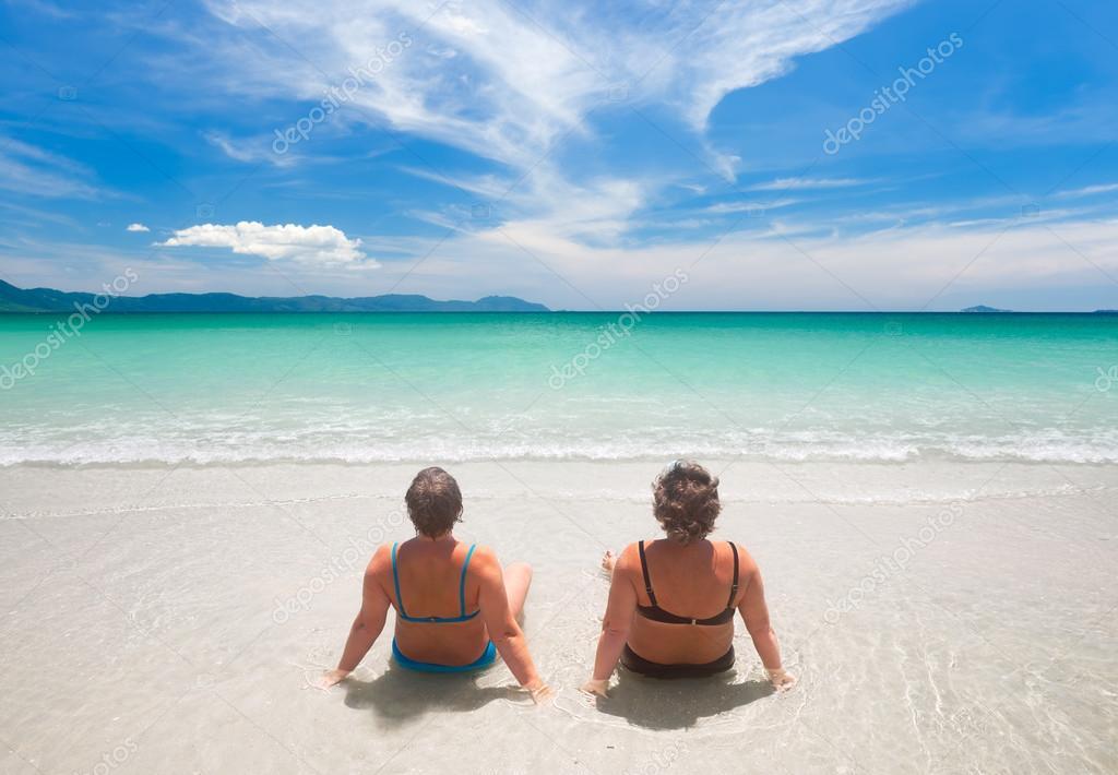 Due mature donna in costume da bagno rilassante sulla spiaggia