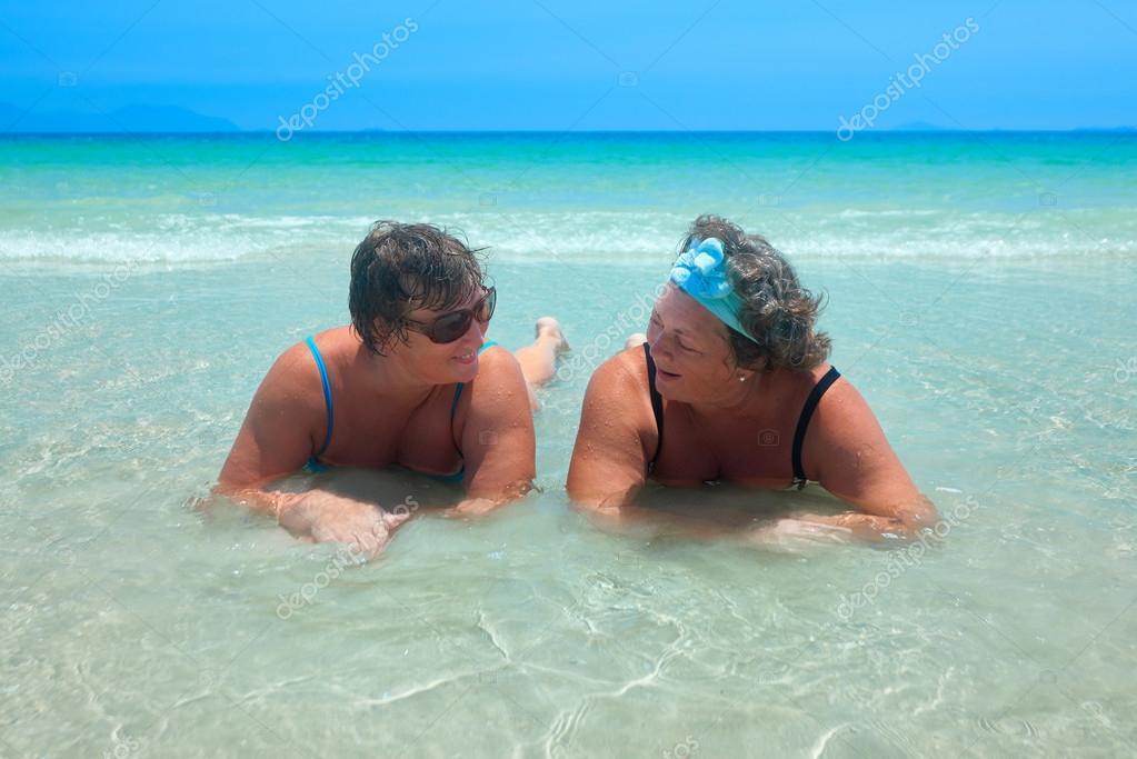 ce84002ee82f Más viejas mujeres en trajes de baño en la playa hablando relajante ...