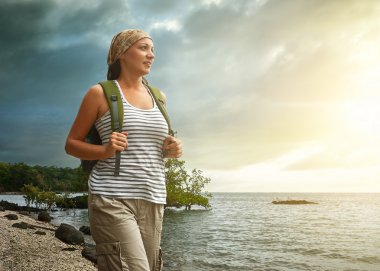 Tourist girl enjoying view of beautiful sunset and sea.