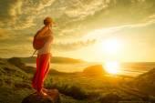 Nő túrázó a tetején állt, és élvezi a naplementét, tengerre néző