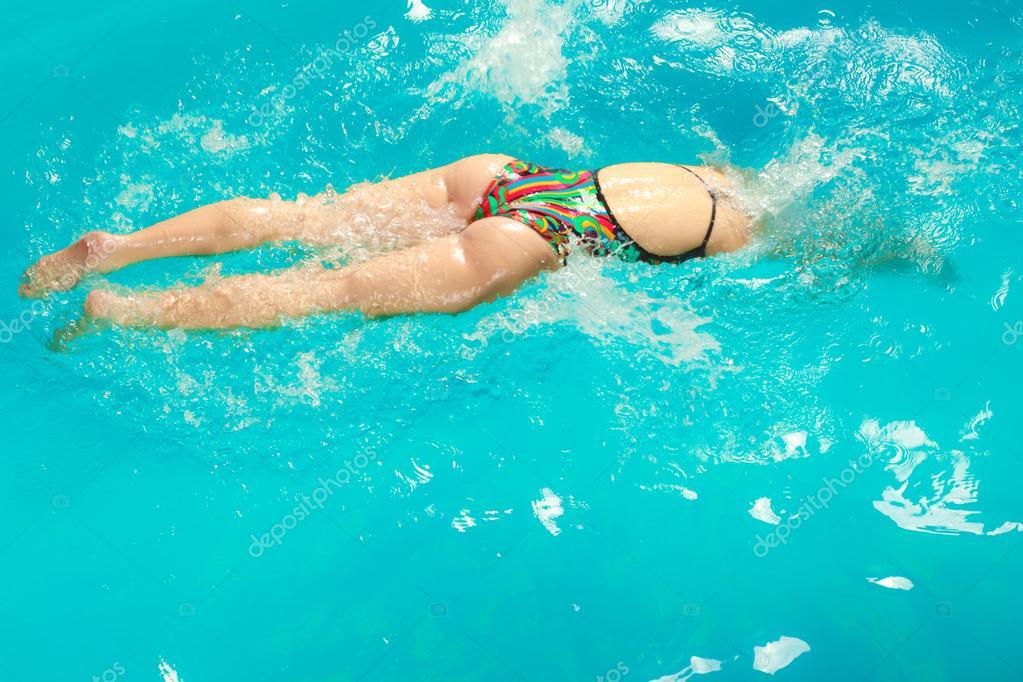 プールでクロール泳法を泳ぐ女性...