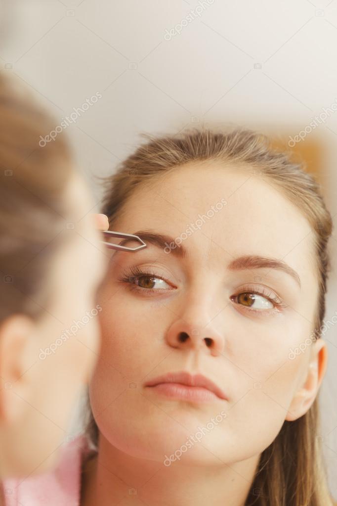 Woman Tweezing Eyebrows Plucking With Tweezers Stock Photo