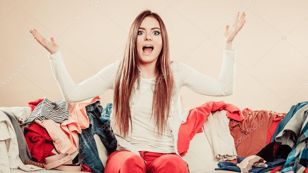 Daily routine in household laundry clothing decision. Worried young woman sit with pile of colorful clothes on sofa. Hands in air and open mouth.