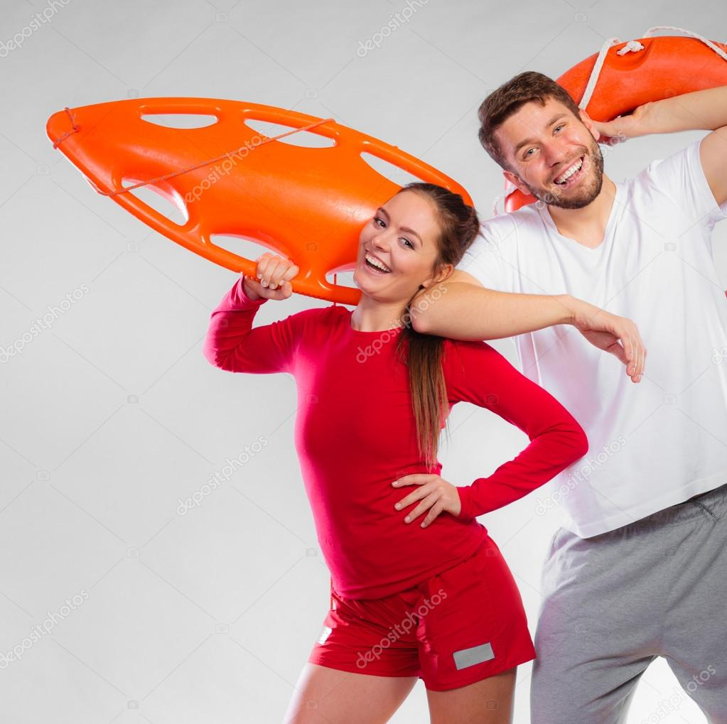 fd701a06756 Accident prevention and water rescue. Young man and woman lifeguard couple  on duty holding ring buoy float lifesaver equipment having fun on gray —  Photo by ...