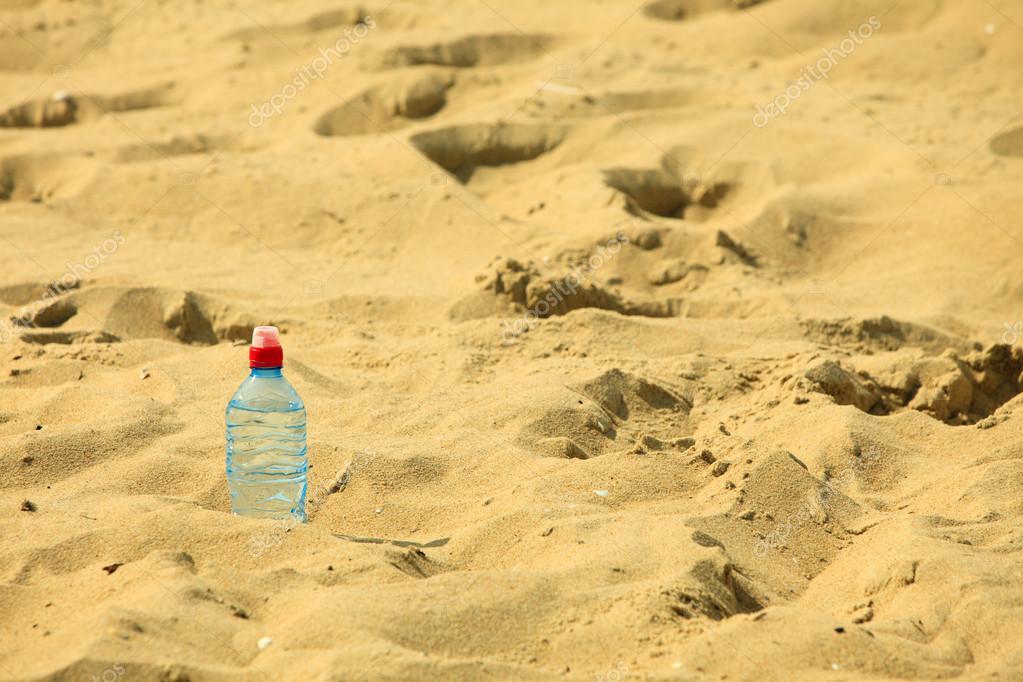 Botella de pl stico en una playa de arena de verano foto for Arena de playa precio