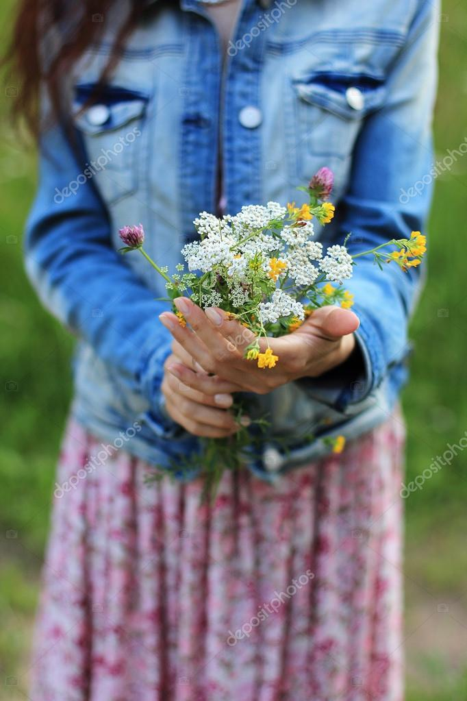 Trendy young woman holding flowers