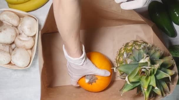 Žena ručně dát ovoce a zeleninu do papírové tašky