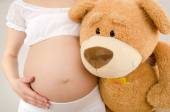 Close up on pregnant belly and a big teddy bear.