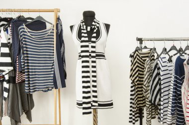 Dressing closet with striped clothes arranged on hangers and a black and white outfit on a mannequin.