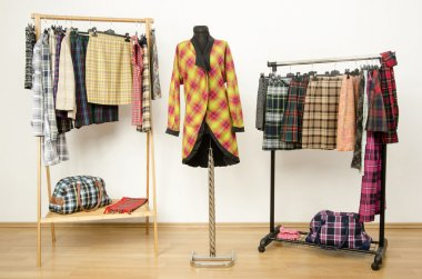 Dressing closet with plaid clothes arranged on hangers and a coat on a mannequin.