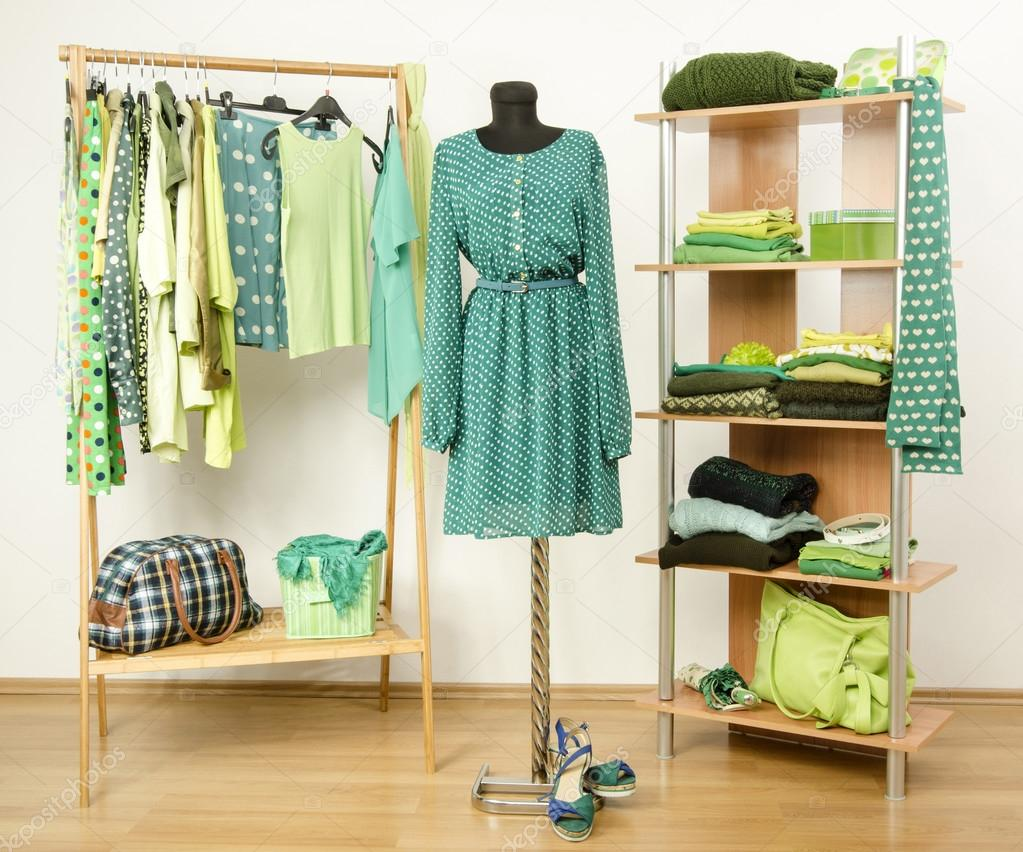 Dressing closet with green clothes arranged on hangers and shelf, dress on a mannequin.