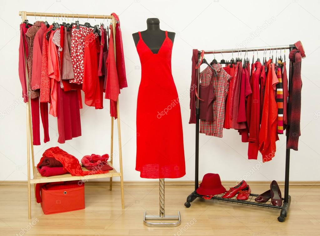 Dressing closet with red clothes arranged on hangers and a dress on a mannequin.