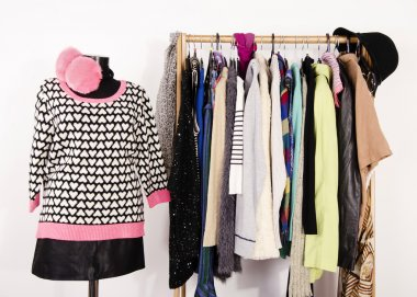 Wardrobe with winter clothes arranged on hangers and an outfit o