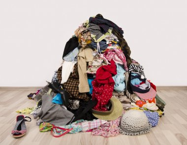 Close up on a big pile of clothes and accessories thrown on the floor.