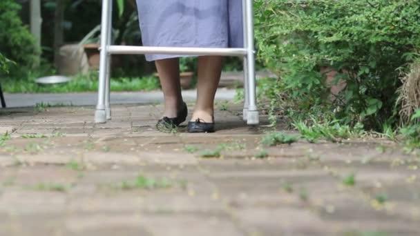 Donna anziana con un camminatore a casa.