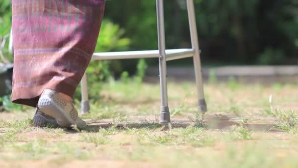Idős nő használ egy walker otthon a kertben.