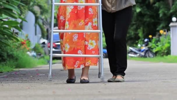 donna maggiore che usando un camminatore attraversare la strada con badante