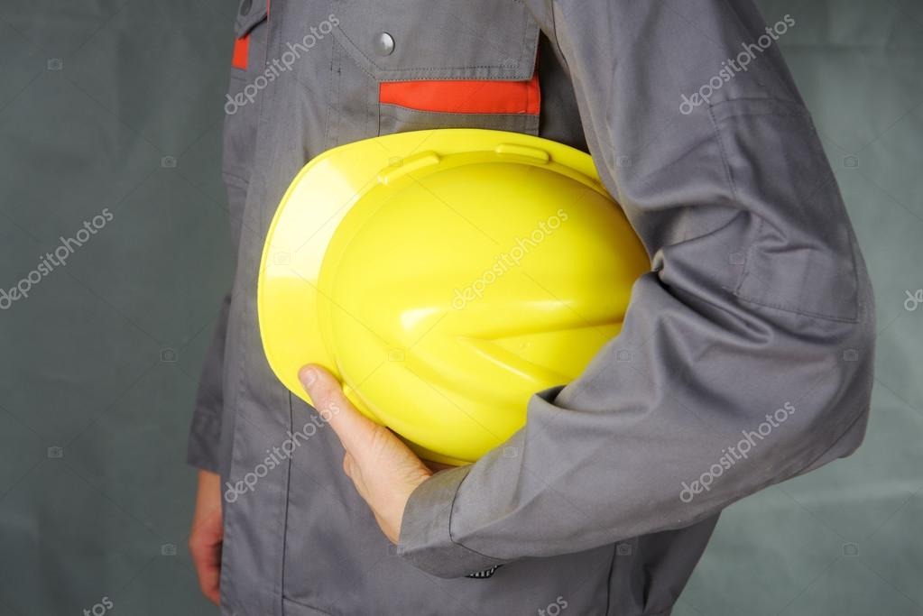 Builder holding helmet in hands