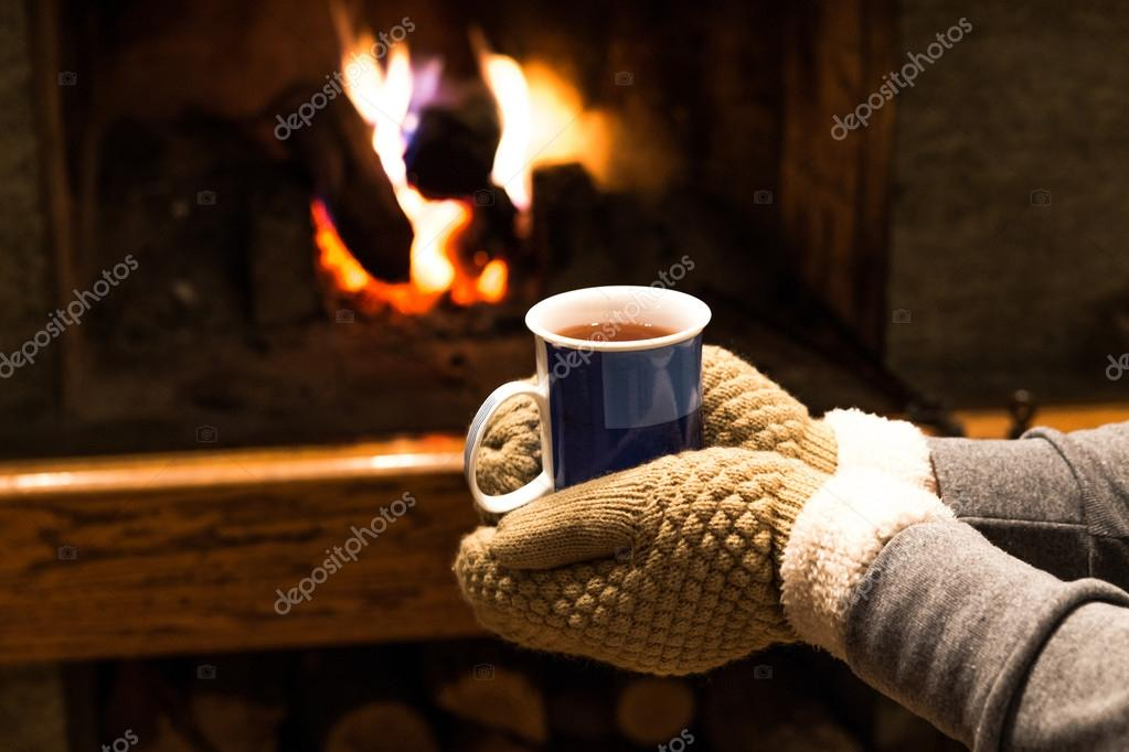 Fireplace Design fireplace background : Holding hot coffee or tea by fireplace — Stock Photo © VioNeta ...