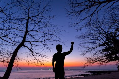 Silhouette man show his hand up in the air with dead tree at sun