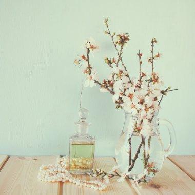 fresh vintage perfume bottle next to white spring flowers on wooden table