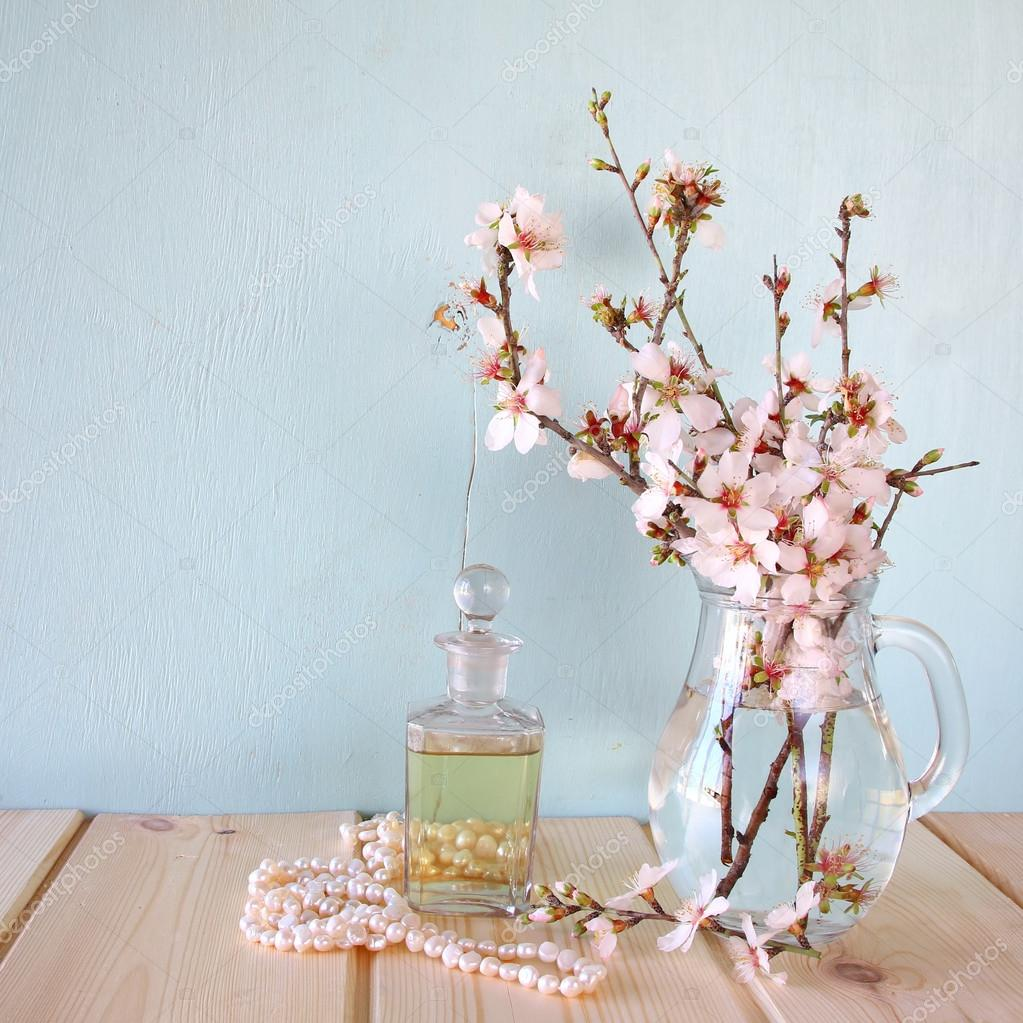 Fresh vintage perfume bottle next to white spring flowers on wooden fresh vintage perfume bottle next to white spring flowers on wooden table foto di tomert mightylinksfo