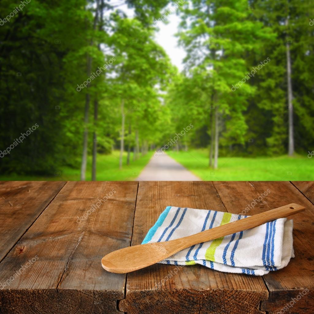 Kitchen utensils on tablecloth on wooden textures table against autumnal forest background