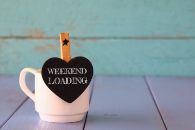 cup of coffee and little heart shape chalkboard with the phrase: WEEKEND LOADING.