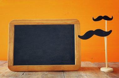 Halloween concept. Blank blackboard next to paper moustache