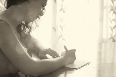 Young woman sitting and writing letter