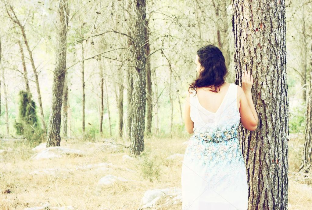 Surreal photo of young woman standing in forest. image is textured and toned