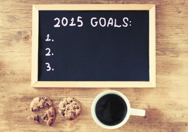 Top view of blackboard with the phrase 2015 goals over wooden board with coffee and cookies