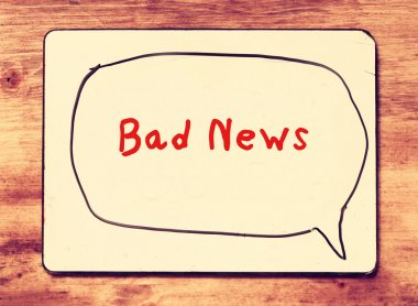 White board with the phrase bad news written on it, over wooden background. filtered image with retro effect.