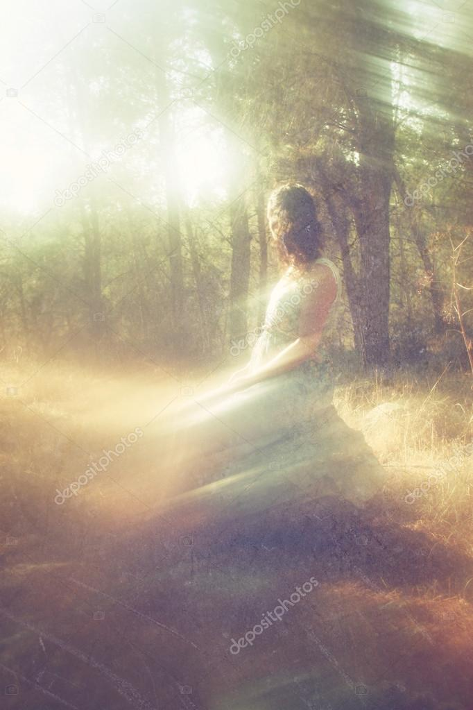 Surreal blurred background of young woman sitting on the tsone in forest