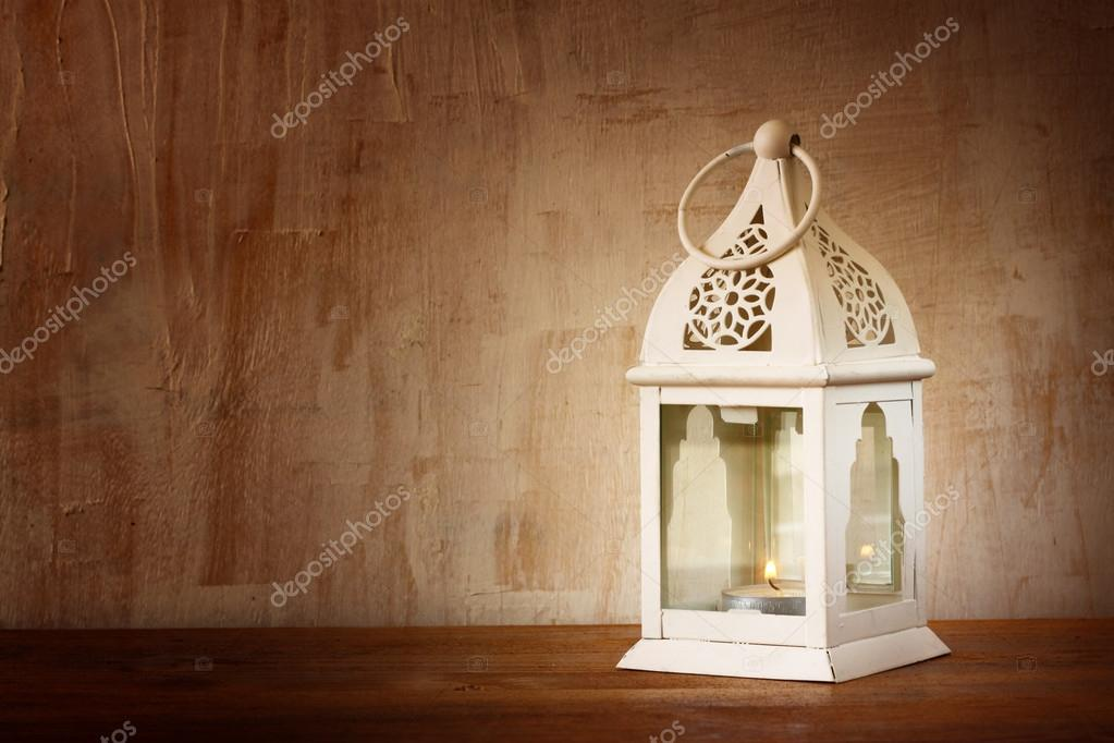 White lantern over wooden table. vintage effect