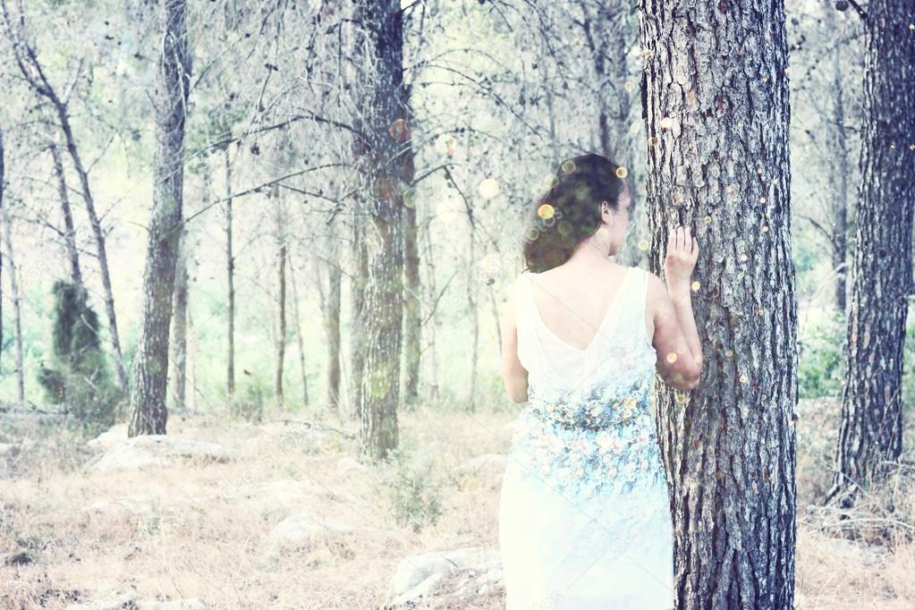 Surreal blurred background of young woman stands in forest
