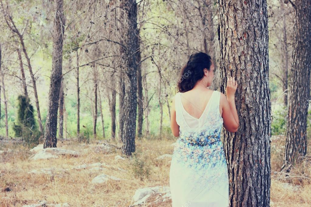 Surreal blurred background of young woman stands in forest. image is retro toned