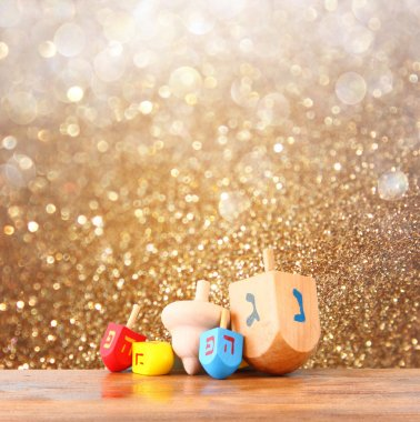 Wooden dreidels for hanukkah and glitter golden lights background