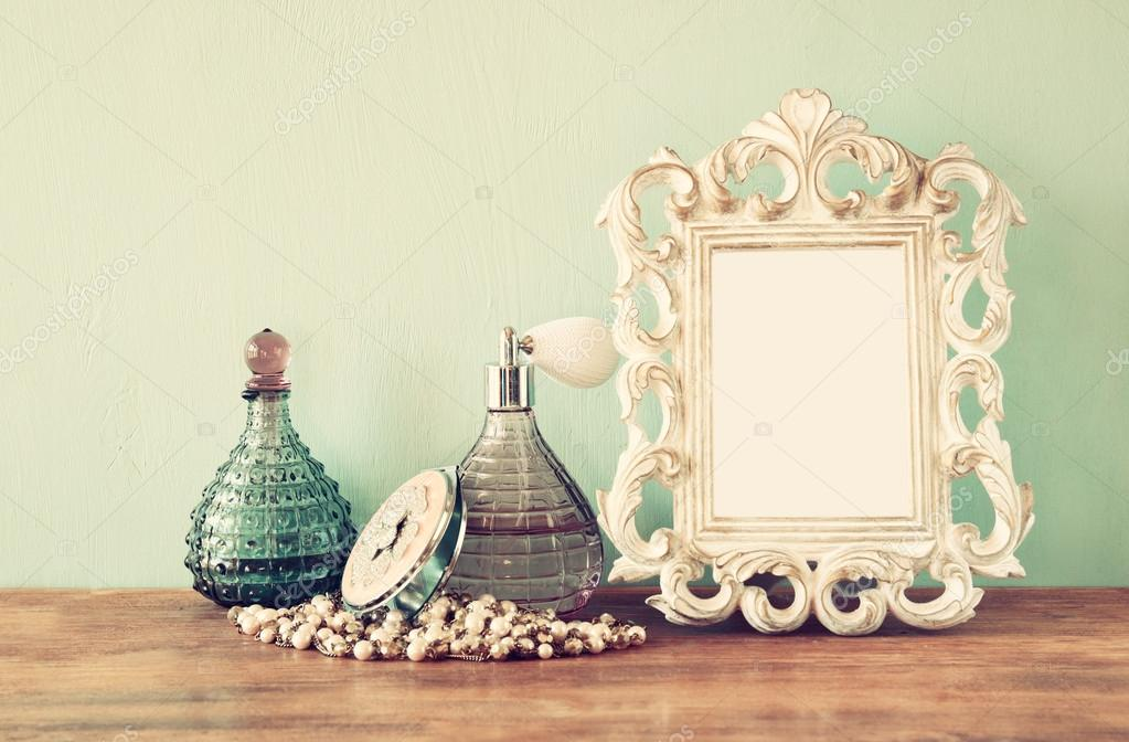 Vintage antique perfume bottles with old picture frame, on wooden table. retro filtered image